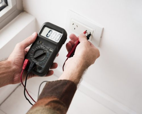 person-s-hand-plugging-digital-multimeter-home_23-2148087608